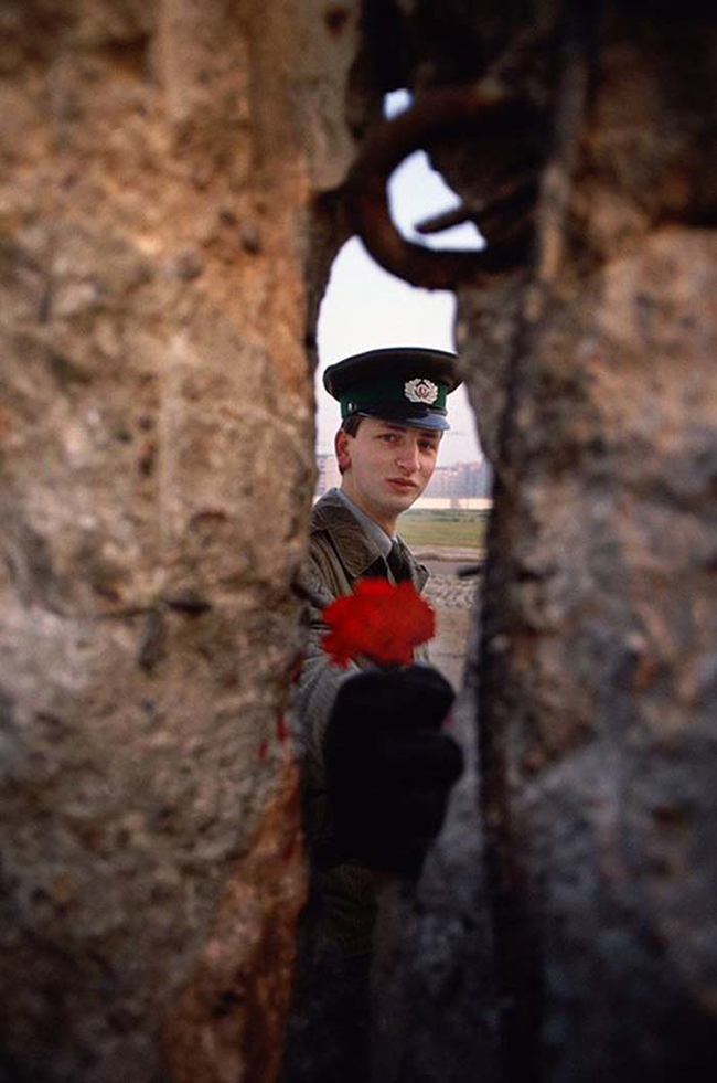 1989 - East German soldier passing a flower through the Berlin Wall before it was torn down. - Imgur