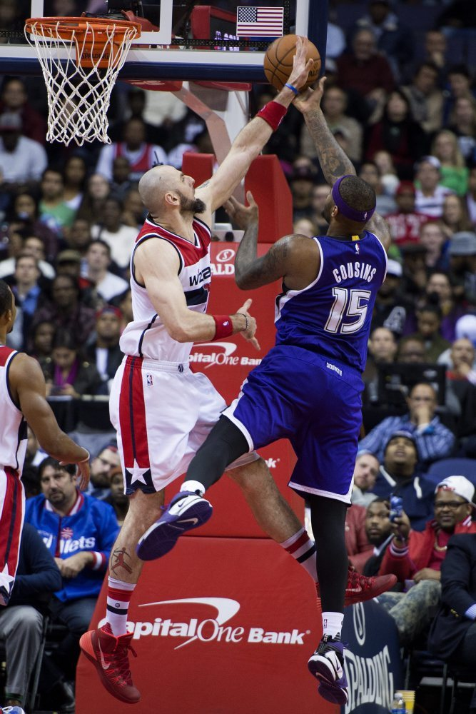 epa05078398 Sacramento Kings forward DeMarcus Cousins (R) shoots against Washington Wizards center Marcin Gortat of Poland (L) during the second half of their NBA game at Verizon Center in Washington, DC, USA, 21 December 2015. The Wizards defeated the Kings 113-99.  EPA/SHAWN THEW CORBIS OUT  Dostawca: PAP/EPA.