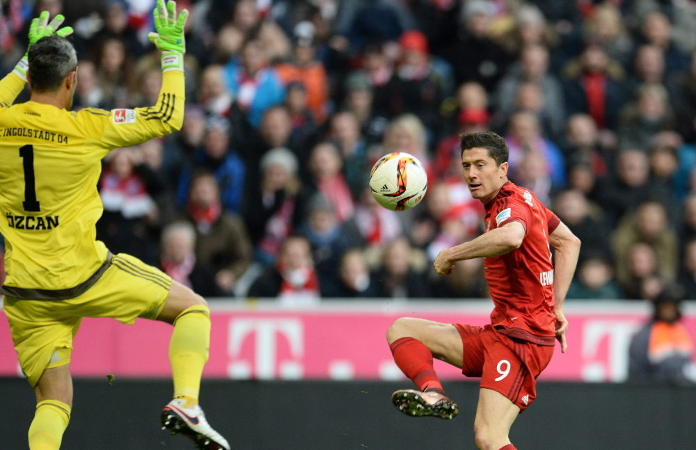 epa05066262 Munich's Robert Lewandowski (R) attempts a goal shot next to Ingolstadt's goalkeeper Ramazan Ozcan during the German Bundesliga soccer match between Bayern Munich and FC Ingolstadt, in Munich, Germany, 12 December 2015.  EPA/ANDREAS GEBERT (EMBARGO CONDITIONS - ATTENTION: Due to the accreditation guidelines, the DFL only permits the publication and utilisation of up to 15 pictures per match on the internet and in online media during the match.)  Dostawca: PAP/EPA.