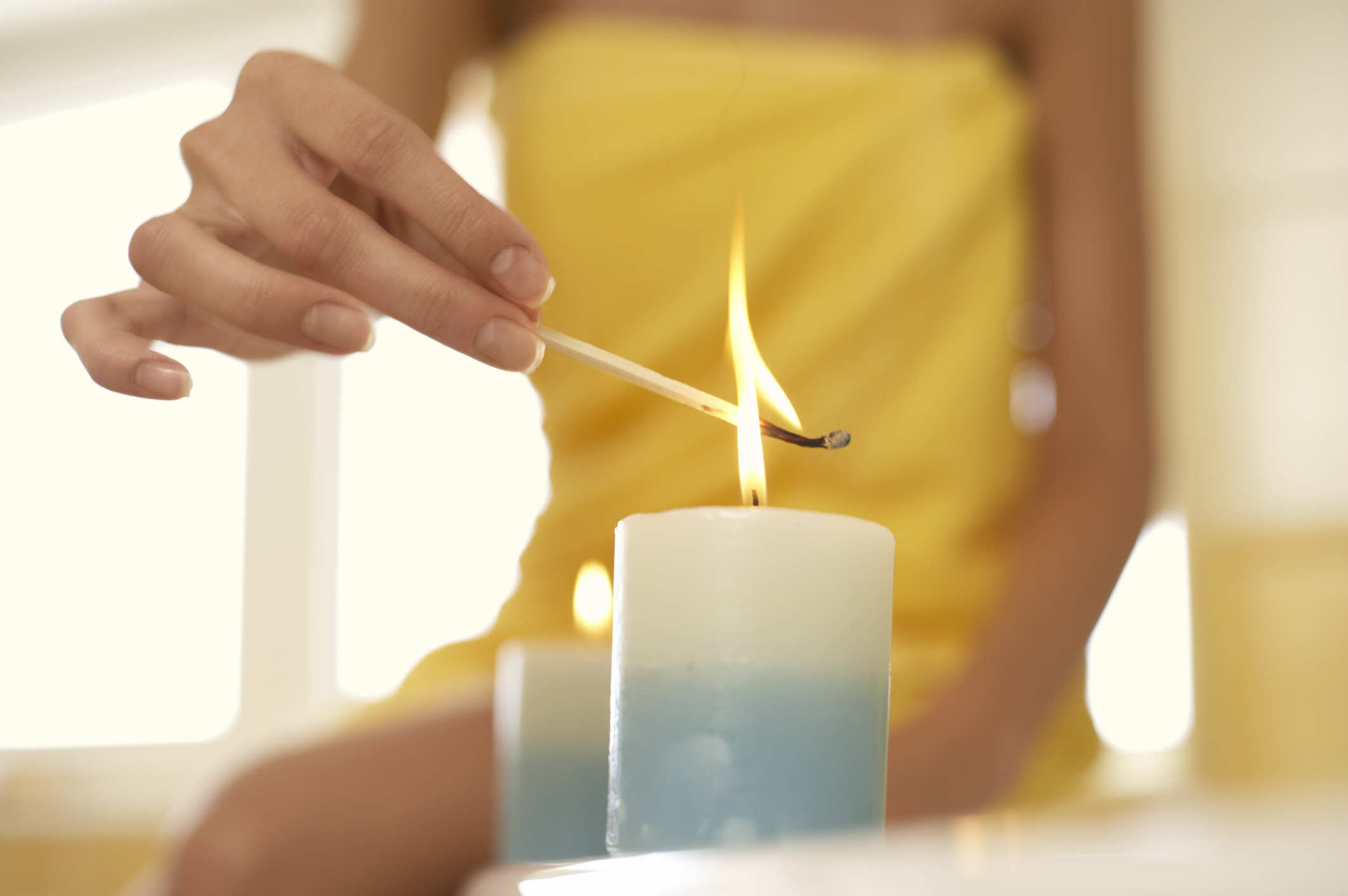 Woman sitting on side of bathtub and lighting aromatherapy candles