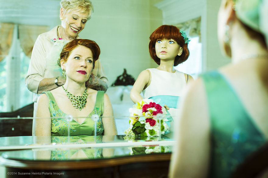 """June 16, 2014 - Denver, Colorado, USA: American Conceptual Photographer, Suzanne Heintz, captures a special moment in a self portrait with her mother and artifical daughter while preparing for a satirical renewal of the vows ceremony. Part of her 14 year photo series, LIFE ONCE REMOVED, in which Heintz satirizes the image of a """"Perfect Life."""" She uses humor to comment on mid-20th Century societal expectations still present for women of a """"Certain Age"""" to marry and have children. She recreates all aspects of family life with her store bought husband and daughter, featuring them in scenes of blissful domestic life in and outside of the home, traditional holidays, and idyllic family vacations. (Suzanne Heintz / Polaris)"""