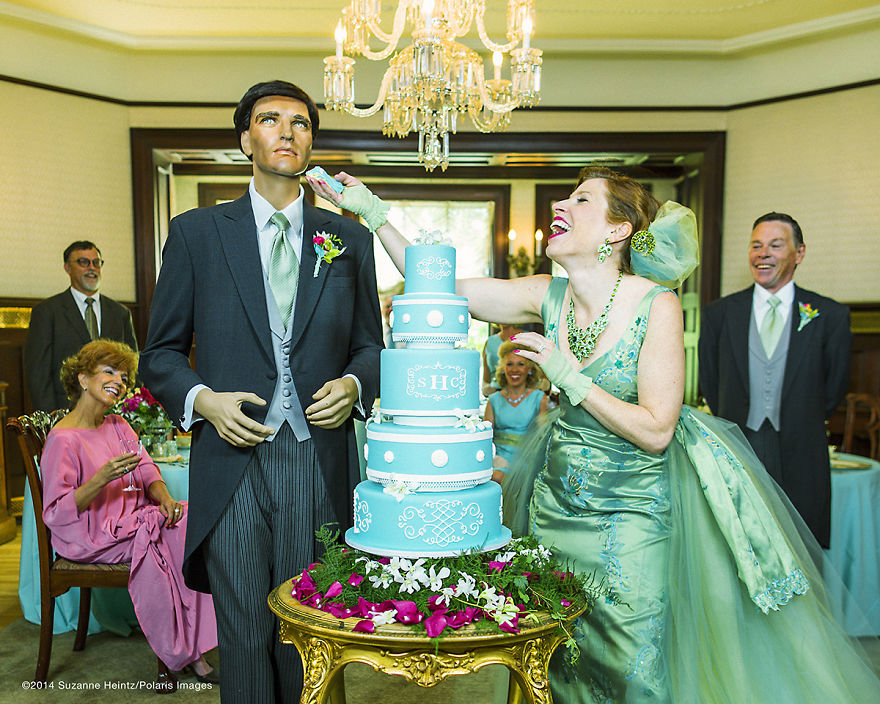 """June 16, 2014 - Denver, Colorado, USA: American Conceptual Photographer, Suzanne Heintz, poses for a self portrait as she feeds her imitation husband a peice of cake after a satirical renewal of the vows ceremony. Part of her 14 year photo series, LIFE ONCE REMOVED, in which Heintz satirizes the image of a """"Perfect Life."""" She uses humor to comment on mid-20th Century societal expectations still present for women of a """"Certain Age"""" to marry and have children. She recreates all aspects of family life with her store bought husband and daughter, featuring them in scenes of blissful domestic life in and outside of the home, traditional holidays, and idyllic family vacations. (Suzanne Heintz / Polaris)"""