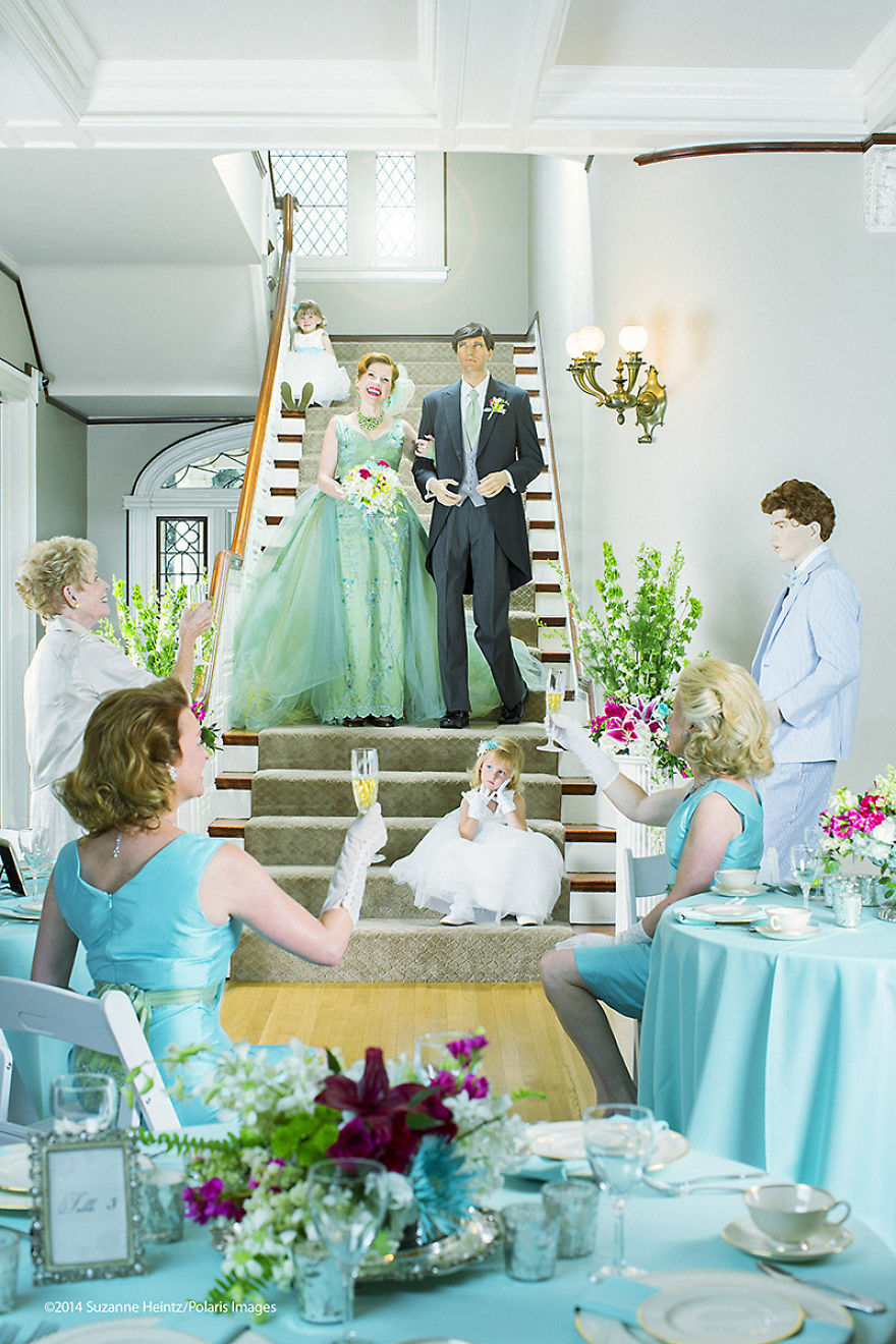 """June 15, 2014 - Denver, Colorado, USA: American Conceptual Photographer, Suzanne Heintz, poses with her imitation husband for a mock renewal of the vows portrait as family and friends raise their glasses. Part of her 14 year self-portrait photo series, LIFE ONCE REMOVED, in which Heintz satirizes the image of a """"Perfect Life."""" She uses humor to comment on mid-20th Century societal expectations still present for women of a """"Certain Age"""" to marry and have children. She recreates all aspects of family life with her store bought husband and daughter, featuring them in scenes of blissful domestic life in and outside of the home, traditional holidays, and idyllic family vacations. Next, she points her satirical lens at the process of Matrimony as she stages a """"renewal of the vows"""" with her manufactured man for her upcoming documentary film, PLAYING HOUSE. (Suzanne Heintz / Polaris)"""