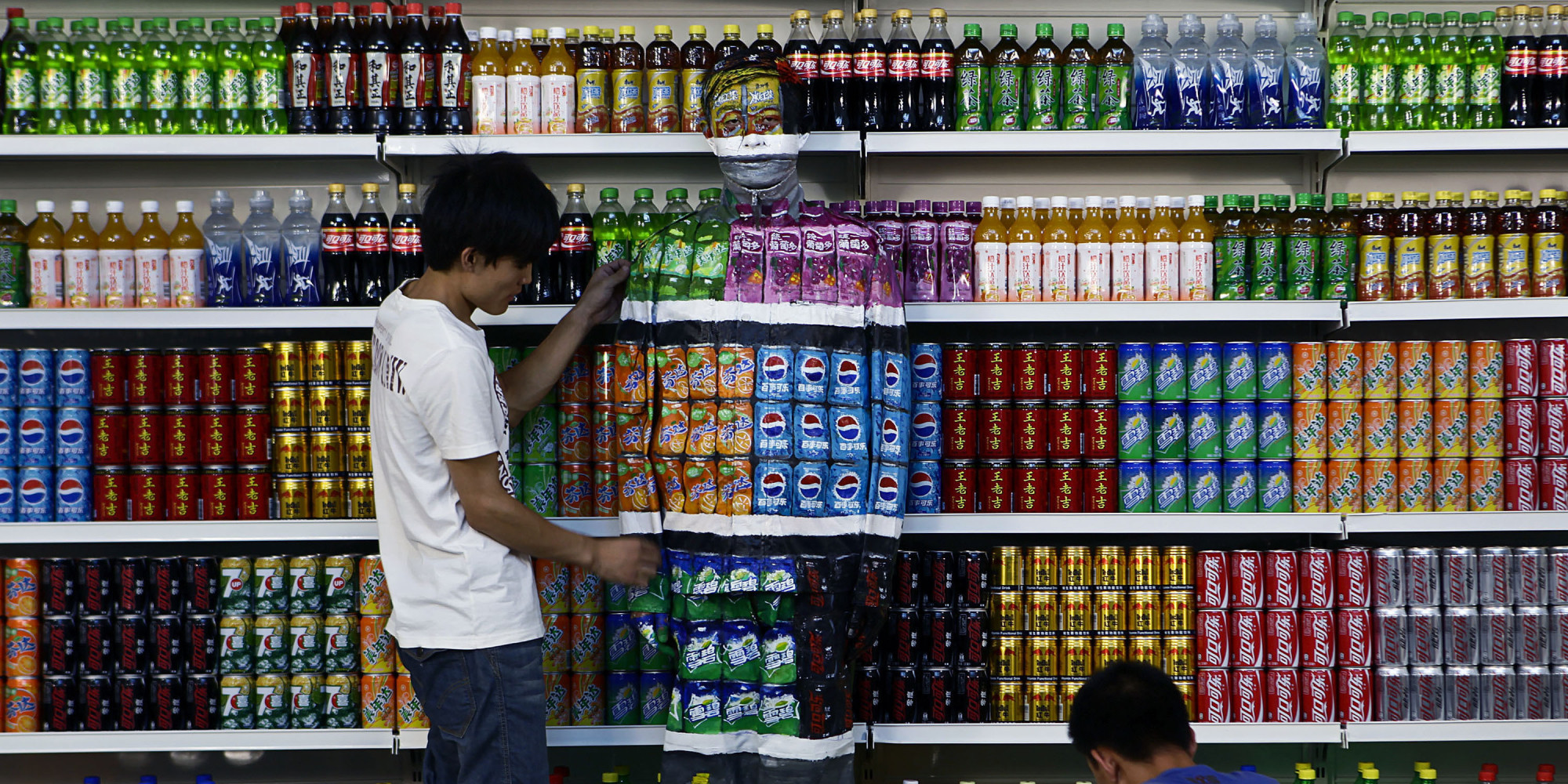 """Chinese artist Liu Bolin, center, is helped by his colleagues as painted to blend into rows of drinks in his artwork entitled """"Plasticizer,"""" to express his speechlessness at use of plasticizer in food additives, in his studio at the 798 Art District in Beijing, China, Wednesday, Aug. 10, 2011. (AP Photo)"""