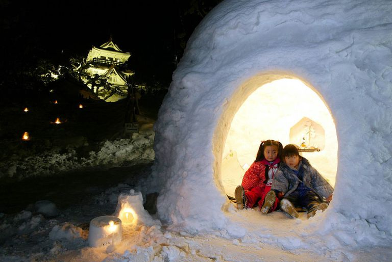 401121 05: Children sit in a snow hut, or kamakura, during the Kamakura Festival February 15, 2002 in the northern Japanese city of Yokote, Akita Prefecture, Japan. During the festival, tourists will be invited into snow huts and served sake and rice cakes. About 100 kamakura huts have been built in the city for the event. (Photo by Koichi Kamoshida/Getty Images)