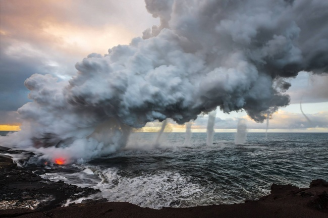 Lava from Kilauea volcano is poured into the sea, creating a huge escape of steam. As it rose, multiple vortices began spinning off of the huge plume. Hawaii.