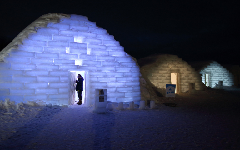 A visitor stands in the doorway to an illuminated room made from snow and ice at night at the Royce' Ice Hills Hotel in Tobetsu, Hokkaido, Japan, on Sunday, Feb. 15, 2015. The seasonal hotel opens from Jan. 17 to March 15 this year. Photographer: Tomohiro Ohsumi/Bloomberg via Getty Images