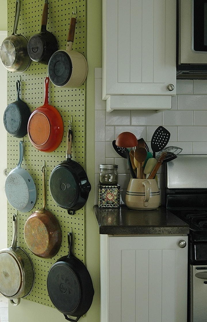A pegboard on the wall for hanging pots and pans.