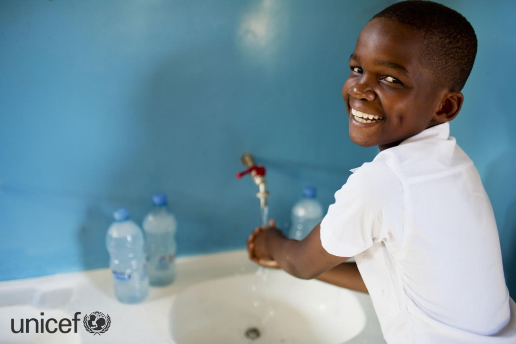 Hans Hasan, a participant of the SWASH club; poses for a photograph while washing her hands at Kingugi School in Dar es Salaam, Tanzania Wednesday, April 2, 2014. The WASH club teaches childrenthe importance of hand washing before eating and after visiting the toilet and encourages children to educate their families and peers of the imporance of having clean hands.