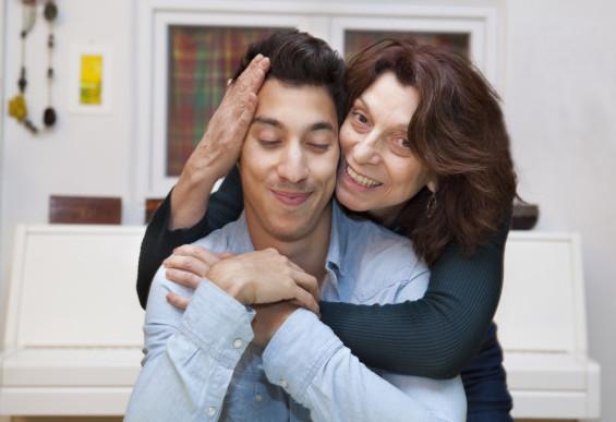 Smiling mother hugging grown son.