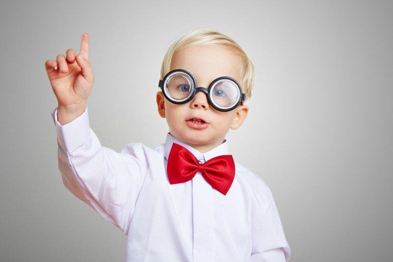 Kind mit dicker Brille und einer Fliege meldet sich in der Vorschule